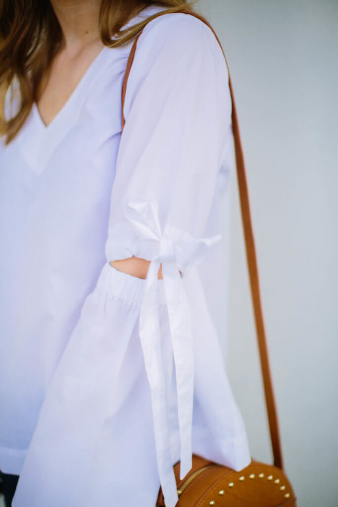 This white bell sleeve vee top is going to be on major repeat well into the summer. The material is super light and breathable, making it the perfect go-to top. I am absolutely in love with the fit, and how darling are the bow details on the sleeves!