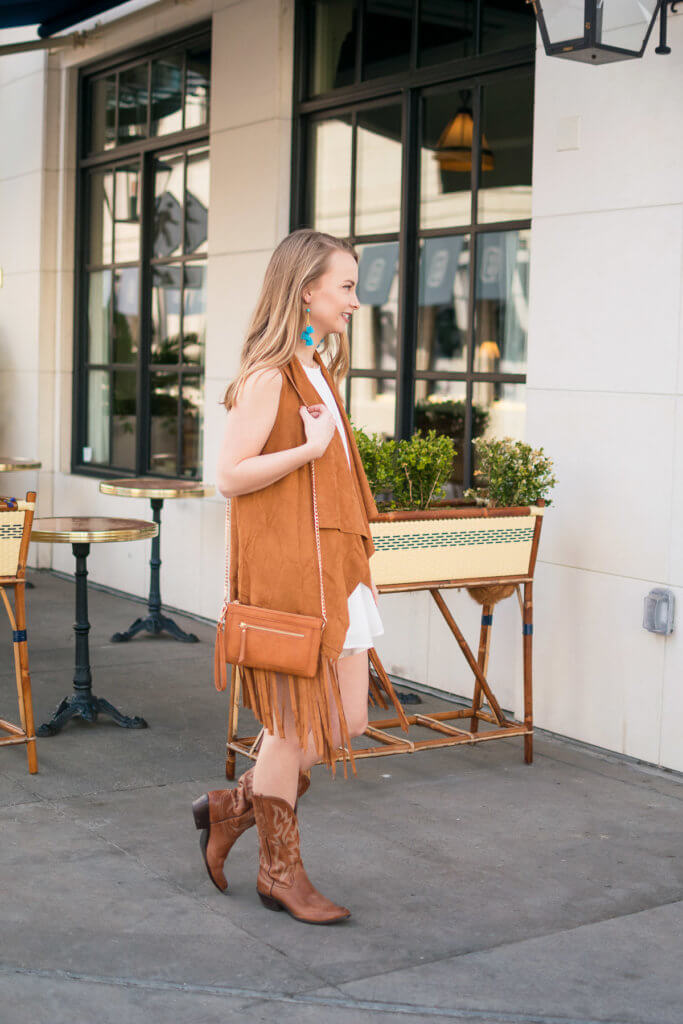 Have you ever wondered what to wear to the rodeo, or how to style your cowboy boots? Click through to shop this gorgeous tan suede vest perfect for rodeo and football season!